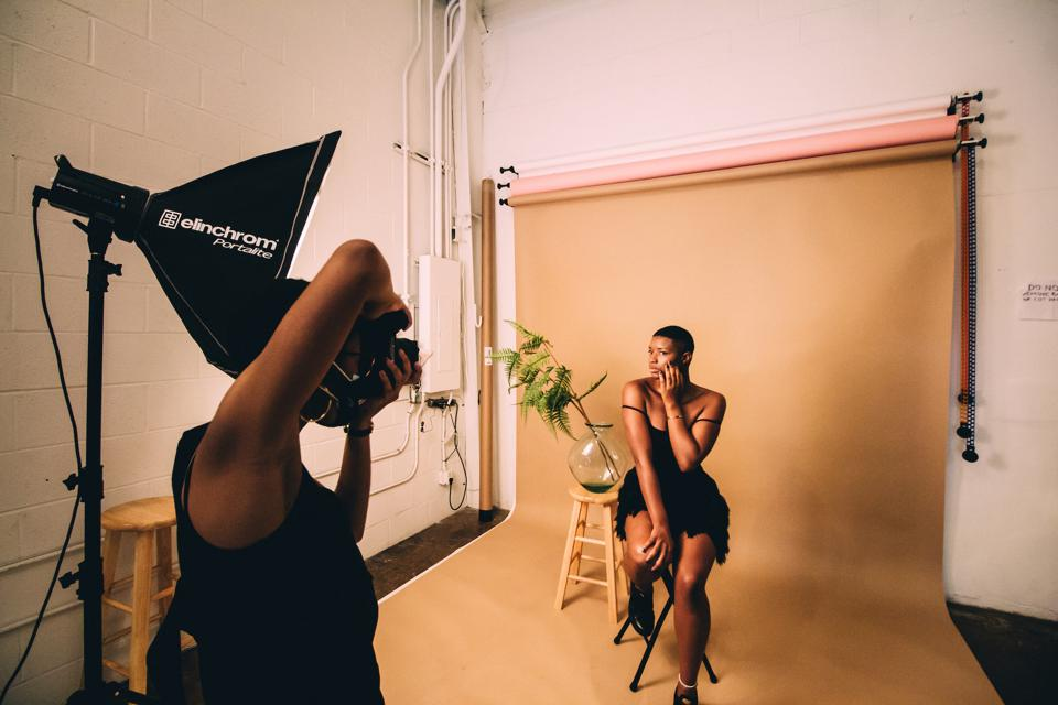 A Black photographer photographs a Black woman dressed in a black dress in photo studio.