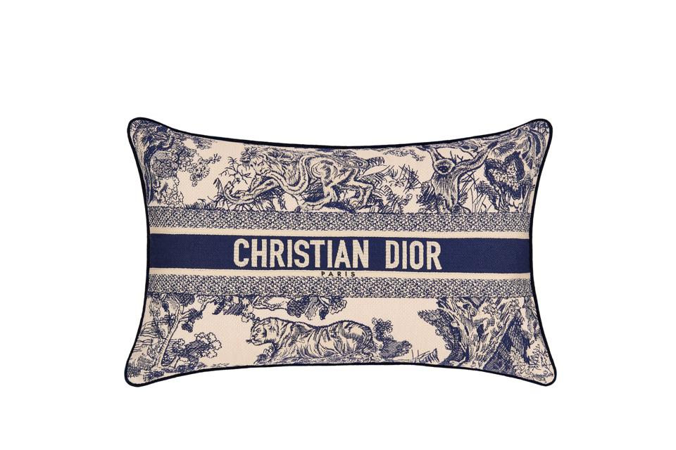 A blue toile pillow with Christian Dior's logo.