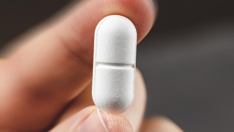 close up view of a hand holding a white pill - health care concept
