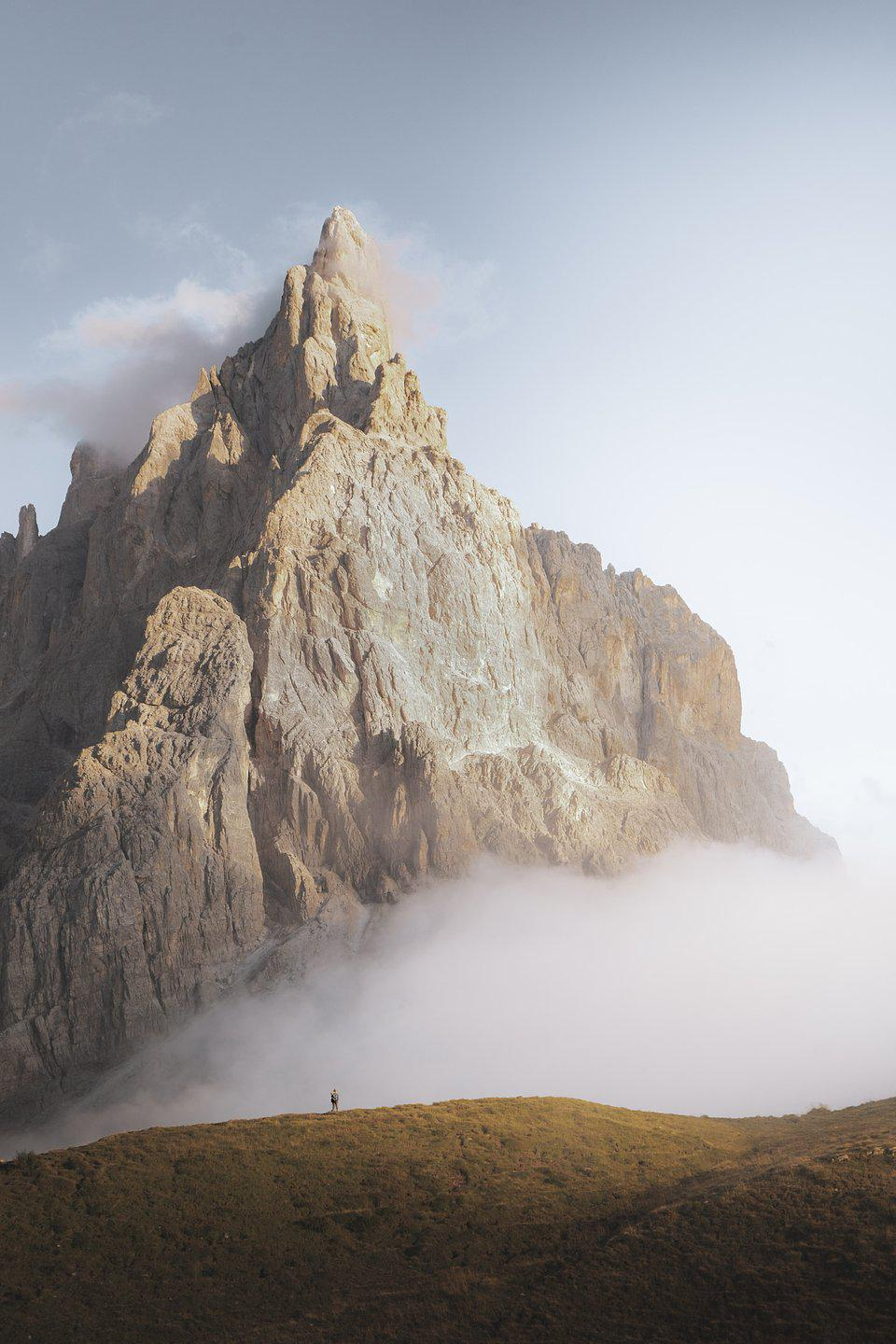 A small figure walking along an immense Dolomite Mountain ridge.