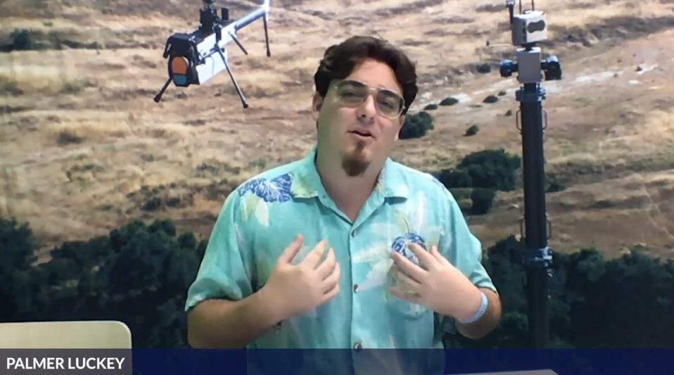 Anduril's Palmer Luckey wearing Hawaiian tee with image of a military drone behind him