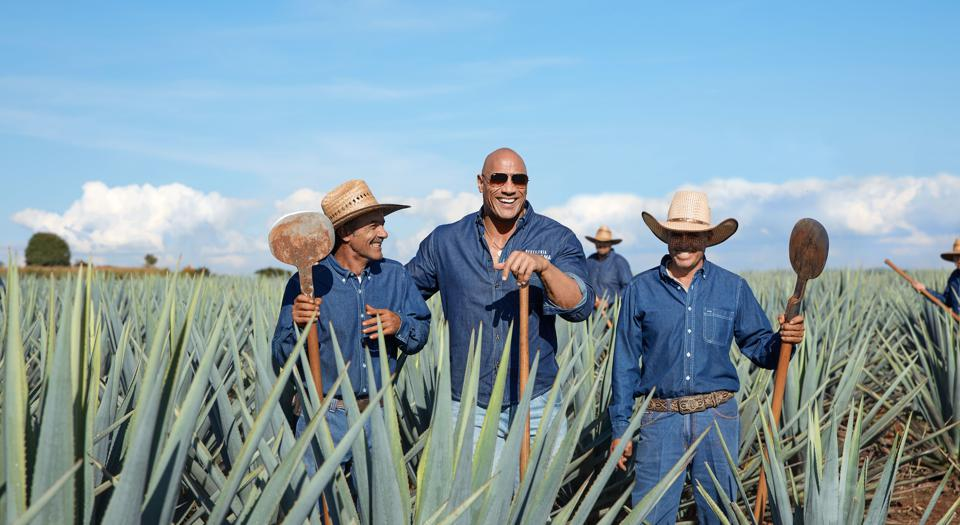 Dwayne Johnson laughs with tequila producers under the Jaliscan sun.
