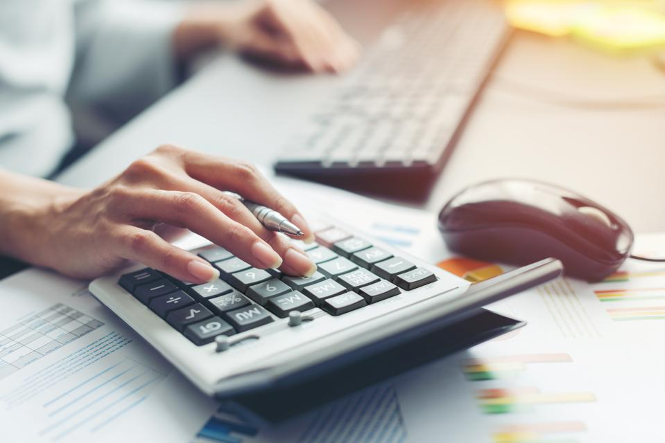 Owner using calculator representing bookkeeping vs. accounting for business owners.