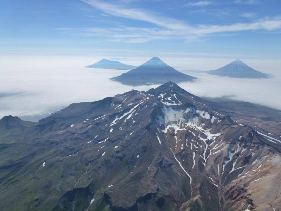 The photo is an aerial oblique view of the volcanoes in the Islands of Four Mountains, Alaska. In the center is the summit of Mount Tana. Behind Tana are (left to right) Herbert, Cleveland, and Carlisle Volcanoes.