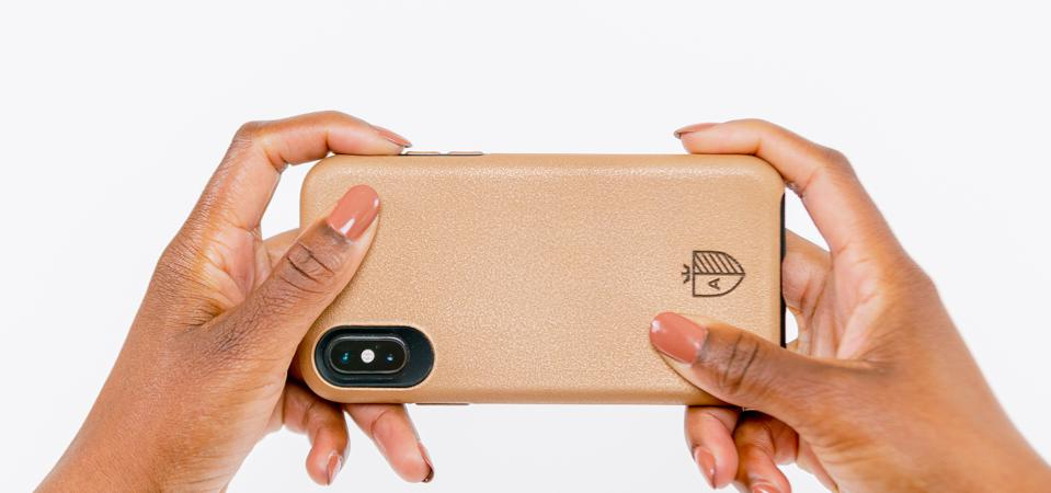Two hands hold the Aeris Copper Phone Case