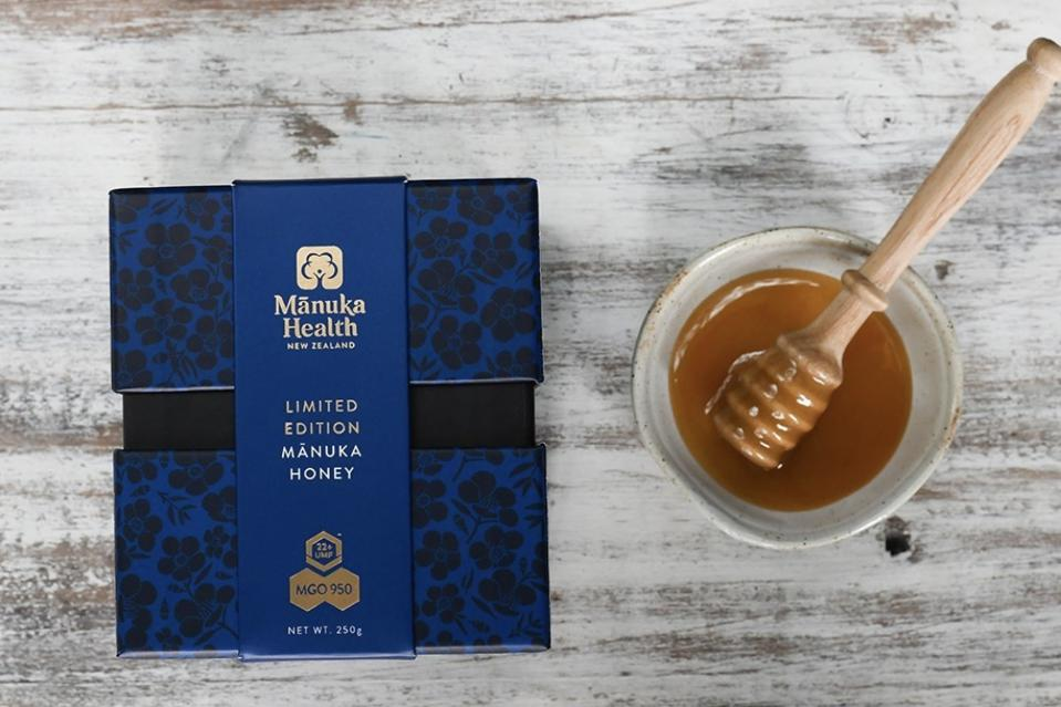 A navy blue box of Manuka Health honey next to a jar of honey on a wood table.