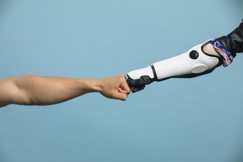 A Human and Robotic Arm Making a Fist Bump