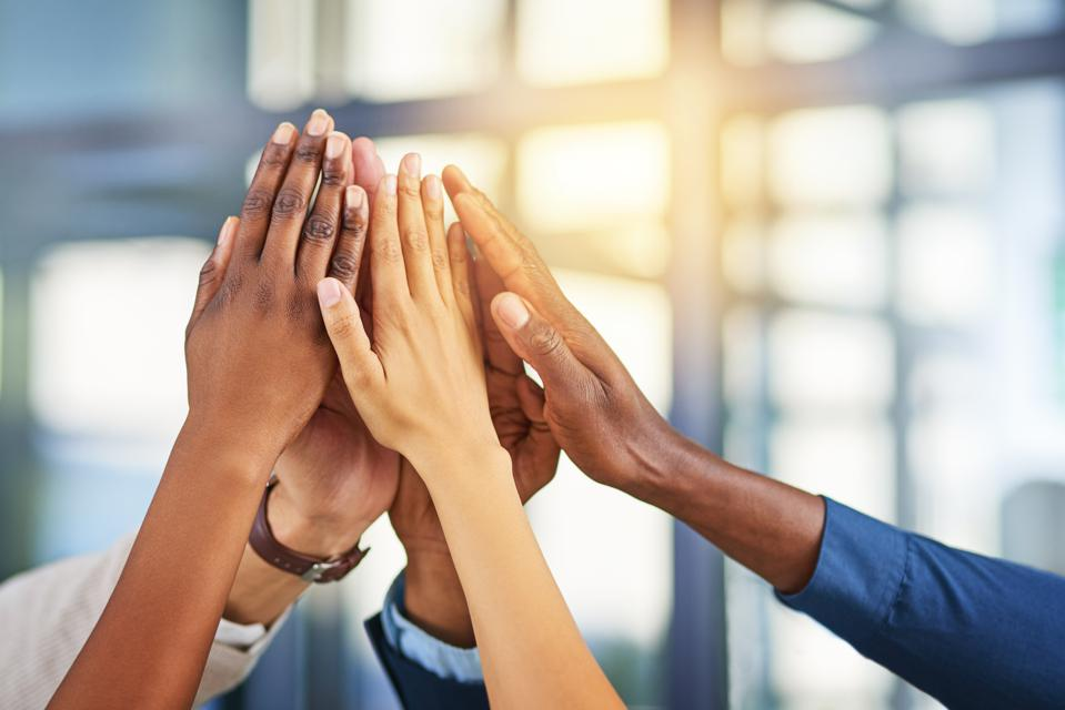 Diverse hands in high five showing importance of a strong network.