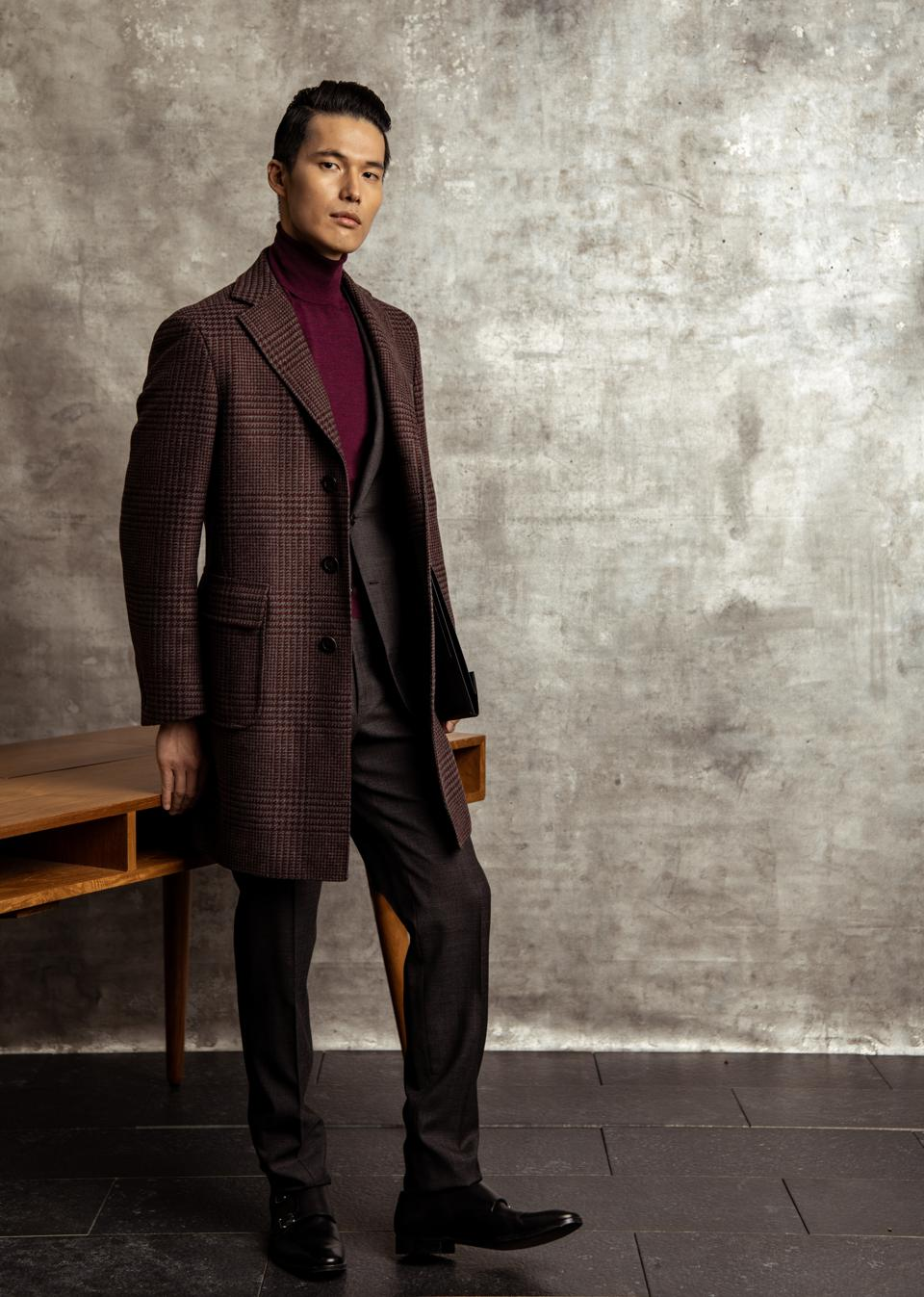 Canali   A single-breasted three-button Kei coat in pure double-faced wool with burgundy and gray Prince of Wales check warp and burgundy weft, notch lapel, flap pockets, and jetted breast pocket. Impeccable pure wool suit in gray and burgundy Prince of Wales check with single-breasted two button jacket with flap pockets, and half-moon breast pocket, and flat-front trousers with quarter-top pockets. This look from Canali elevates the everyday business look by combining classic corporate elements with contemporary details.  Price in USD :  Coat: $2,390.00 Full Suit: $1,690.00 Knit: $350.00  Brand URL/ Hyperlink : www.canali.com  Brand handle and relevant brand hashtags @canali1934