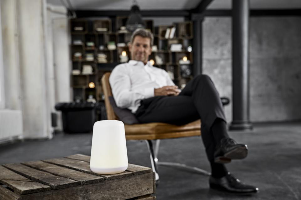 Mature man using voice-controlled digital assistant in loft