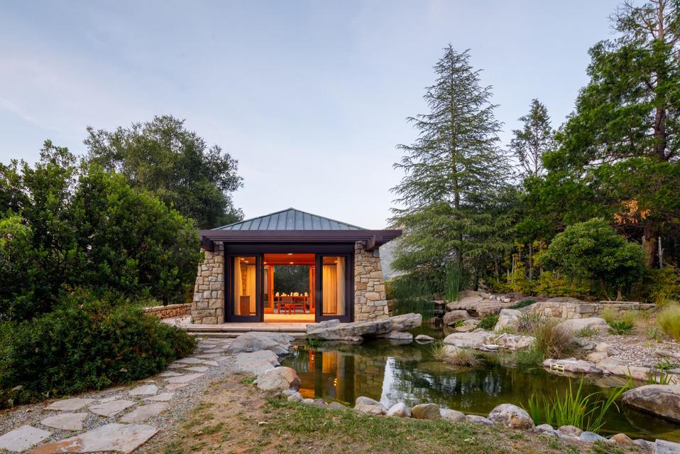 A meditation room set next to a pond.