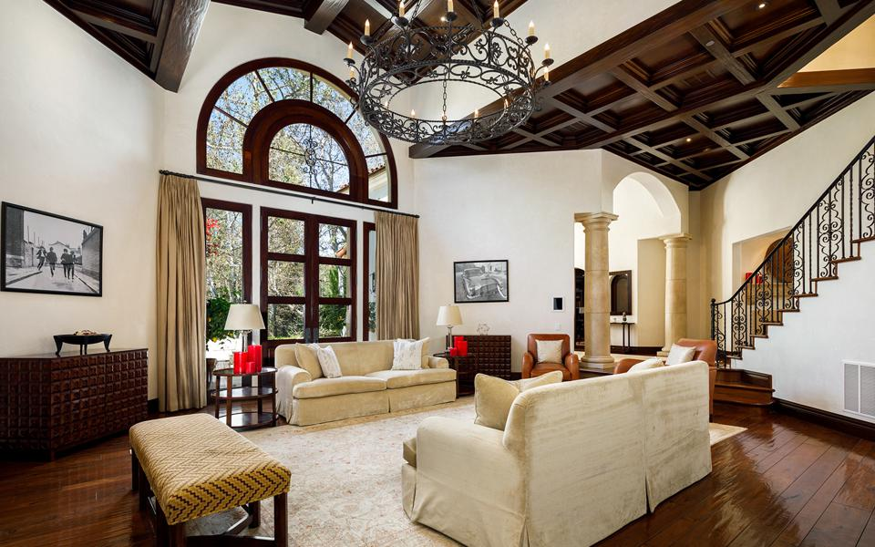 A two-story living room with a wrought-iron chandelier and palladian-style windows.