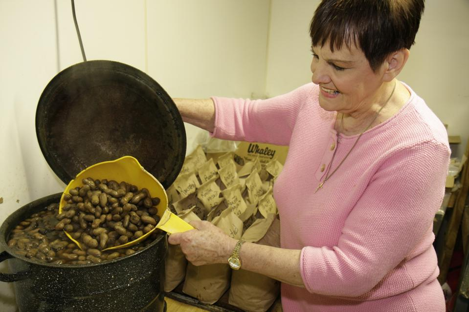A woman boiling peanuts in the Bama Nut Shop.