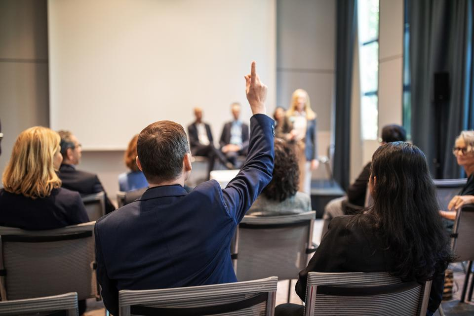 Businessman raising hand to ask question in seminar