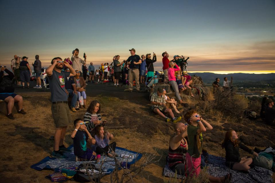 People seen watching the total solar eclipse over the town of Prineville in Oregon during 2017's ″Great American Eclipse.″