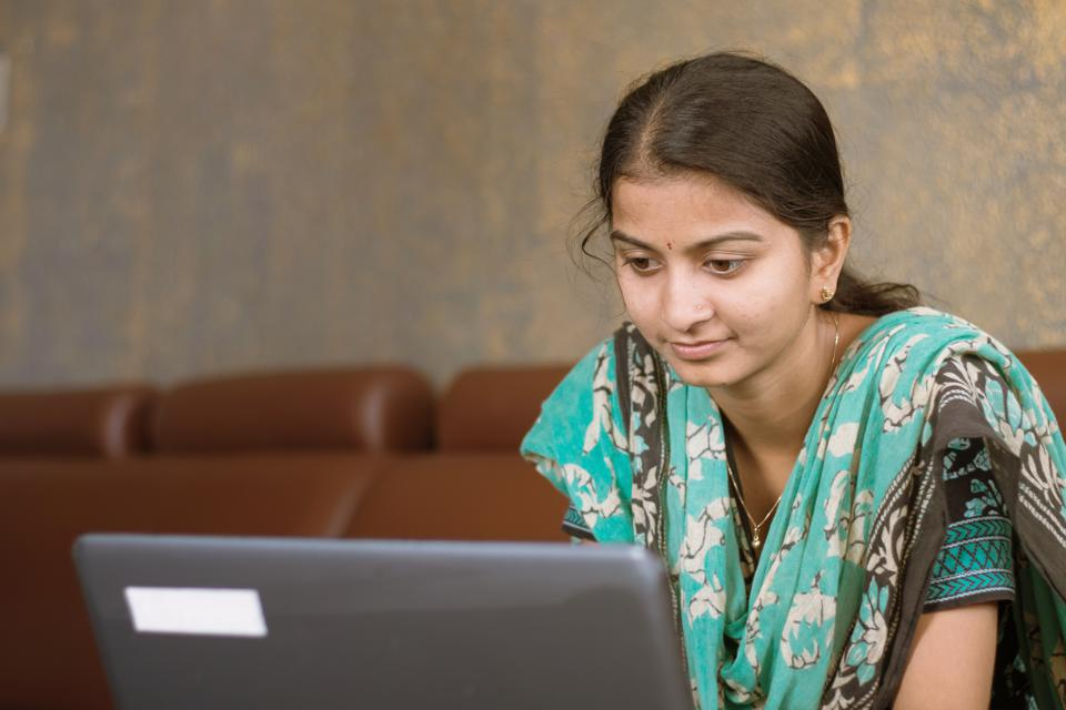 Smiling indian girl student or employee busy on laptop sit at home in casual dress, happy woman studying, e-learning, using online software or technology app for work, education concept