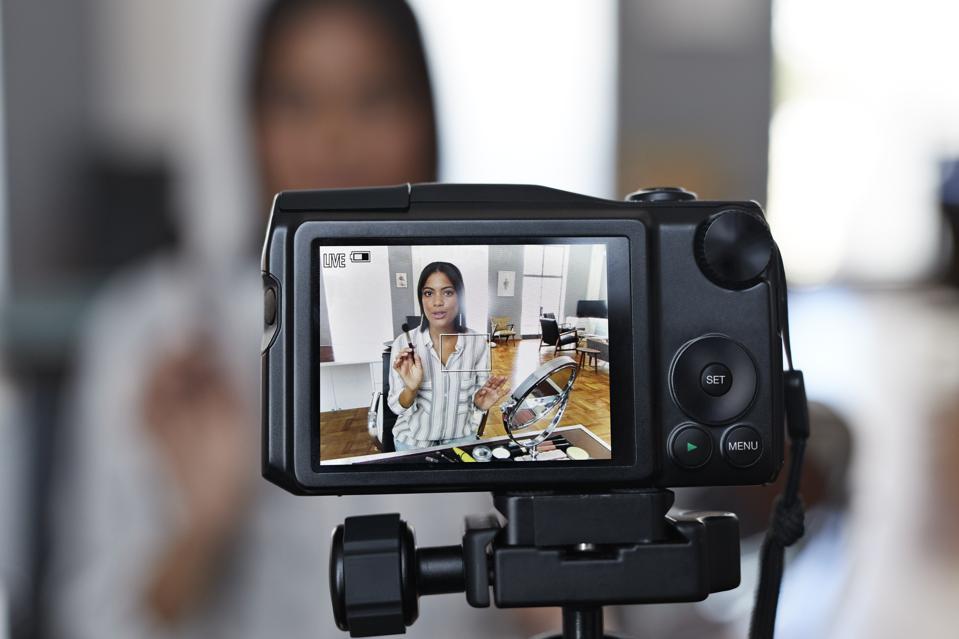 Female influencer recording make-up tip videos for her blog