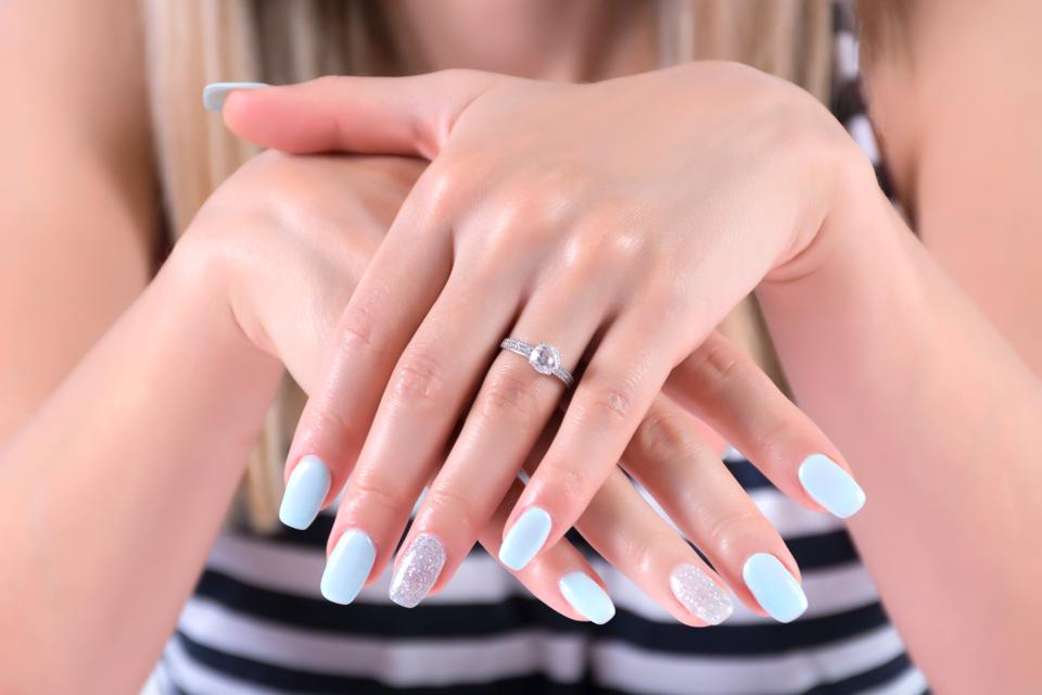 Girl hands with blue nails polish manicure and diamond engagement wedding rings