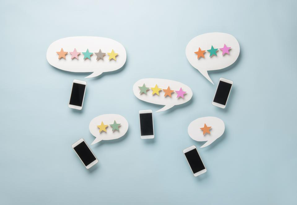 Wooden five star shape with Chat Bubble and smart phone.