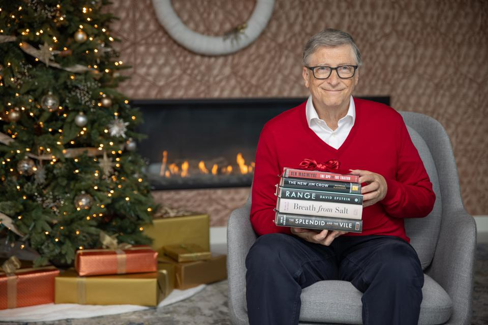 Bill Gates wearing red sweater holding books next to Christmas tree.