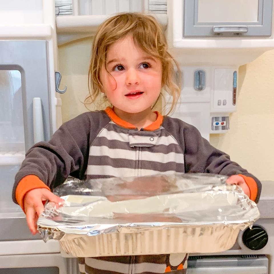 three-year-old girl carrying a tray of covered food