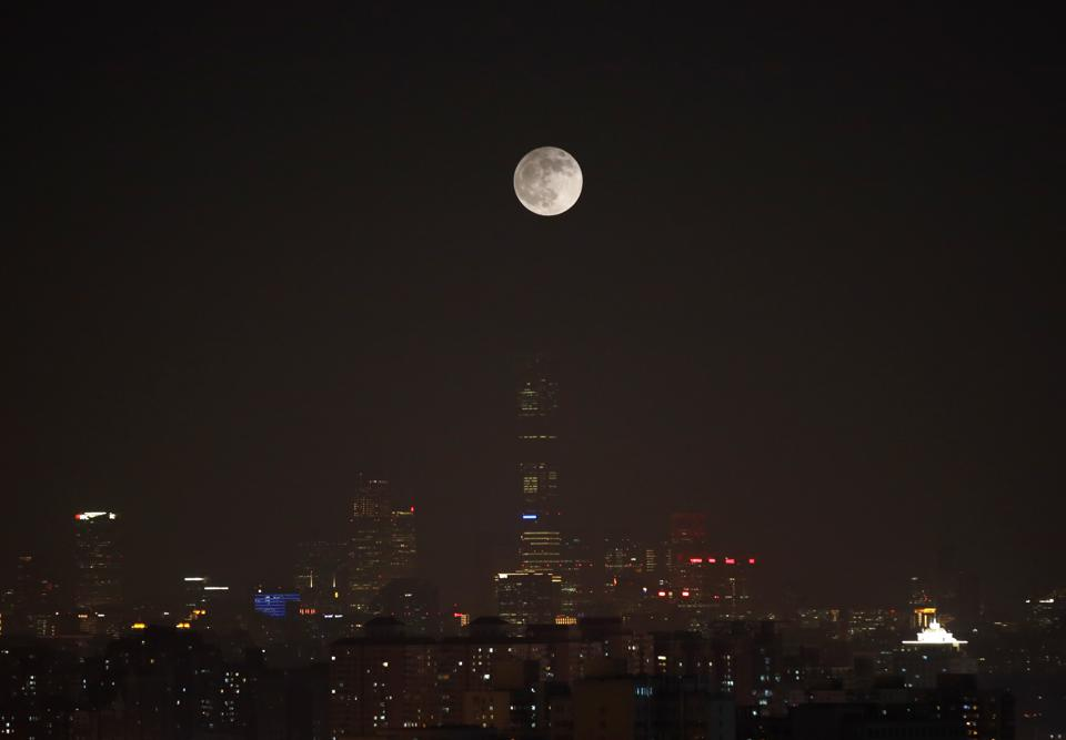 The moon is seen above the Beijing, China skyline during a penumbral lunar eclipse.