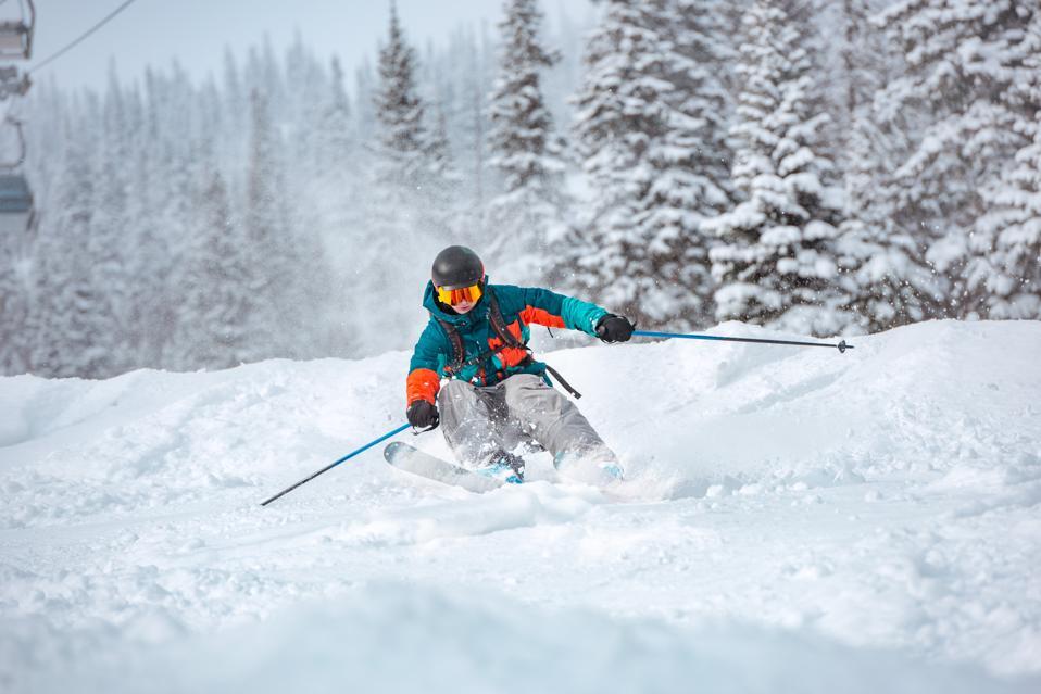 Freeride skier at off-piste slope in forest