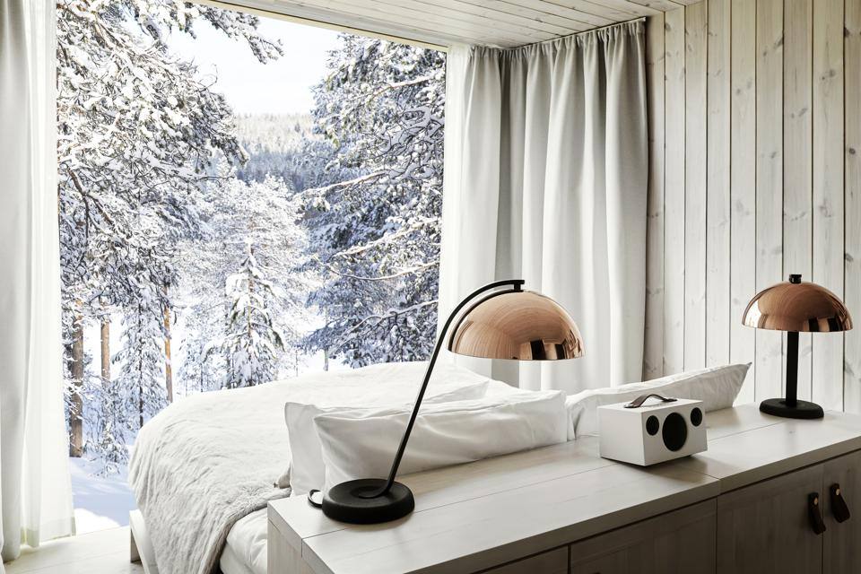 A whitewashed room with the bed facing a floor to ceiling window and snowy trees outside.