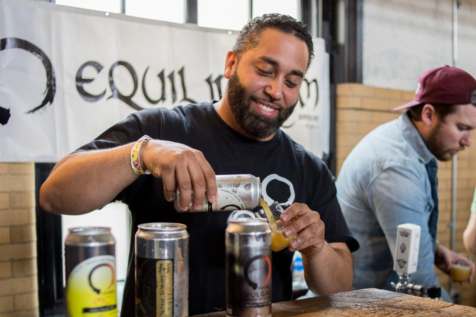 A beer industry professional pours a glass at a Hop Culture event.
