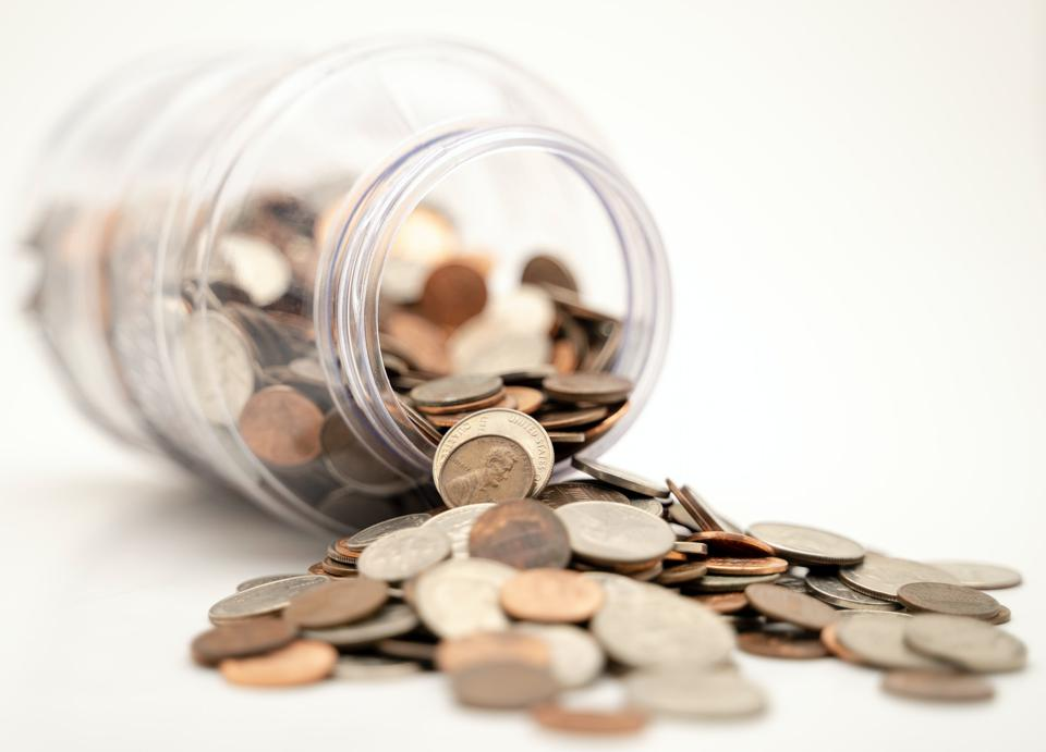 Coins spilling out of jar - personal finance.