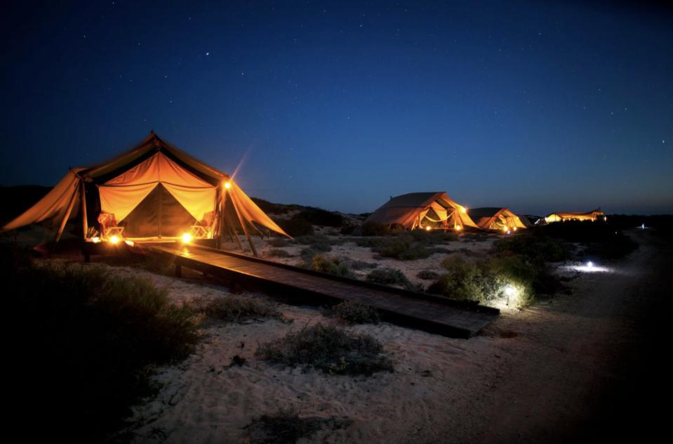 Lighted tents along the ocean from Original Travel Company.