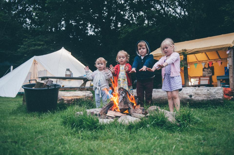 Little ones warming their hands at a campsite.