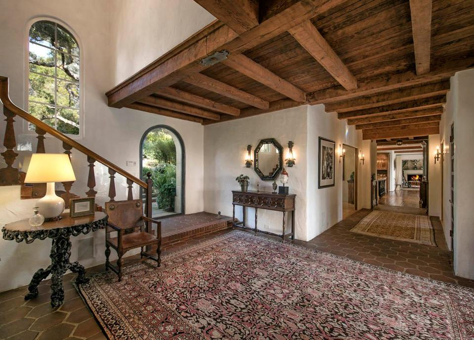 A wide hallway with a wooden ceiling leads to the main living spaces.