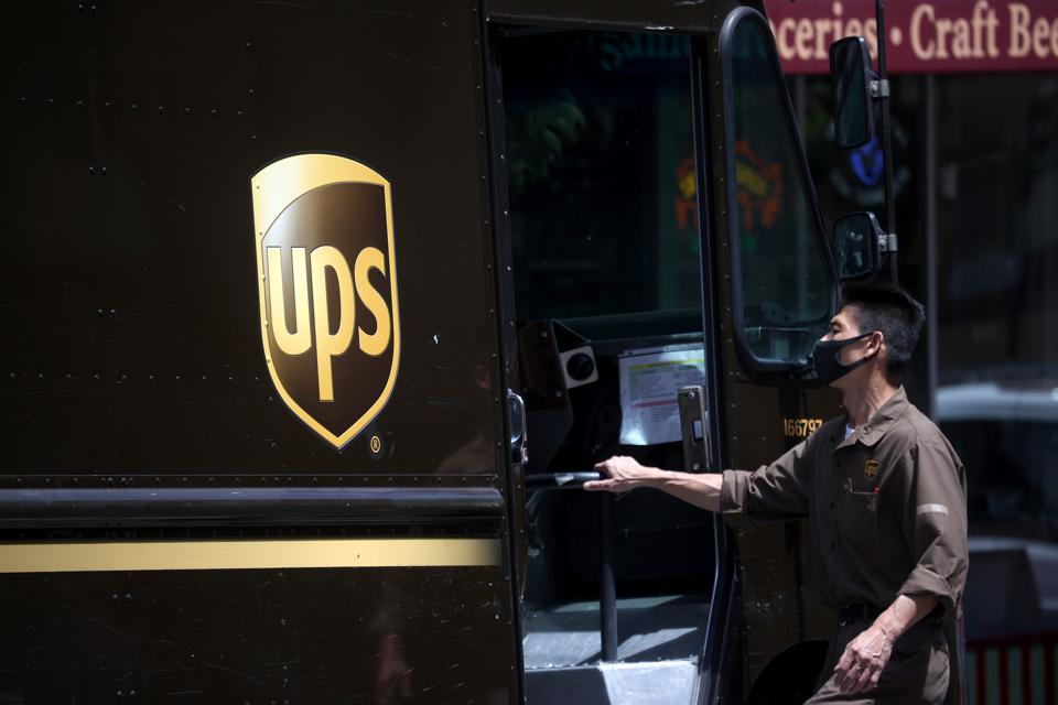 A United Parcel Service (UPS) driver gets into his truck while on his delivery route.
