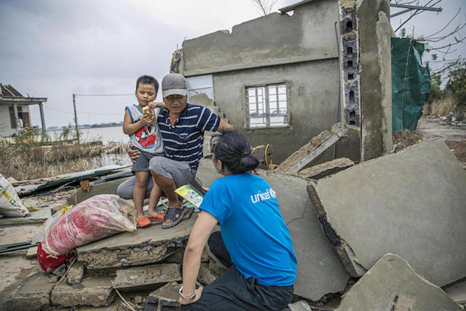 Chu Huu Trang, UNICEF Communication for Development Specialist, talks to Mr Duong Van Nam and his visually impaired son in the ruins of their home.