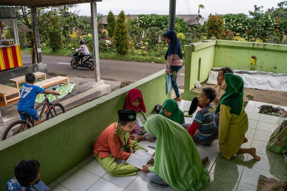 Twelve-year-old Syaiful (center, in orange) studies the Quran with classmates in a UNICEF-supported inclusive education program at Madrasah Ibtidaiyah in Banyumas, Central Java, Indonesia.