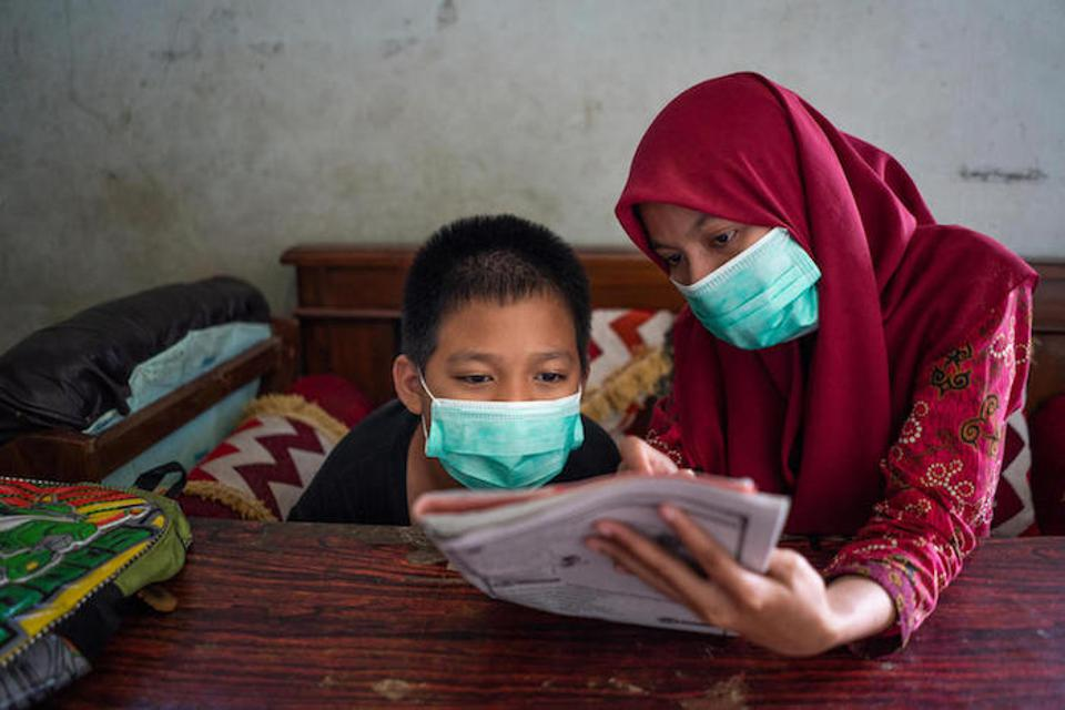 Syaiful studies with his UNICEF-trained teacher, Fatikhatus, at his grandfather's home in Banyumas.