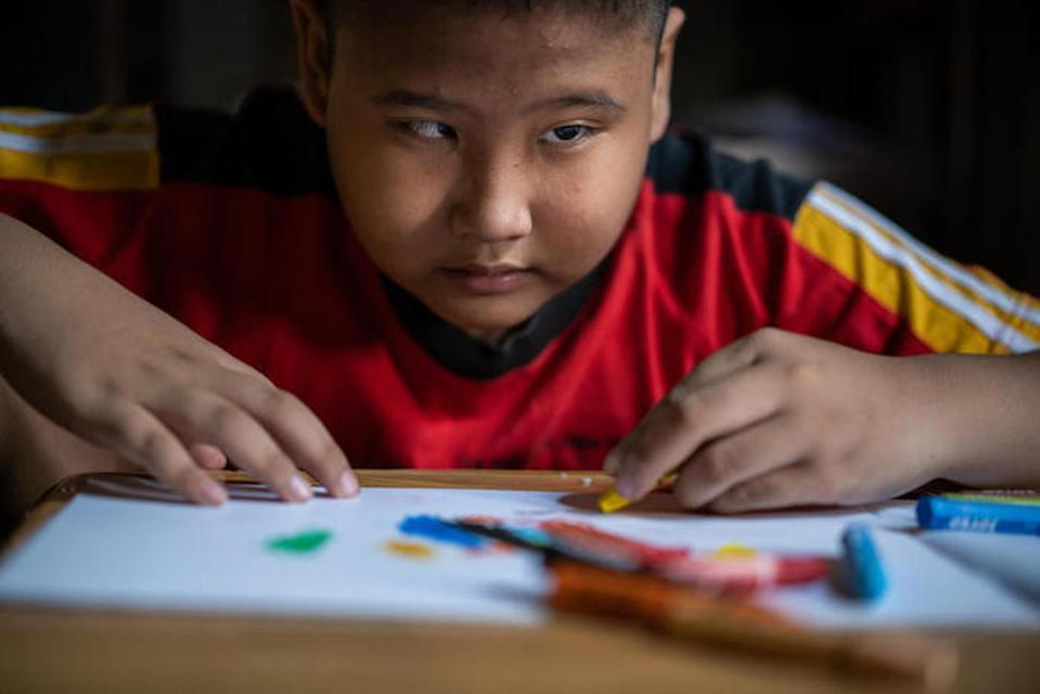 Nine-year-old Kevin, a student at Madrasah Ibtidaiyah who has a visual impairment, works on a drawing at home in Banyumas.