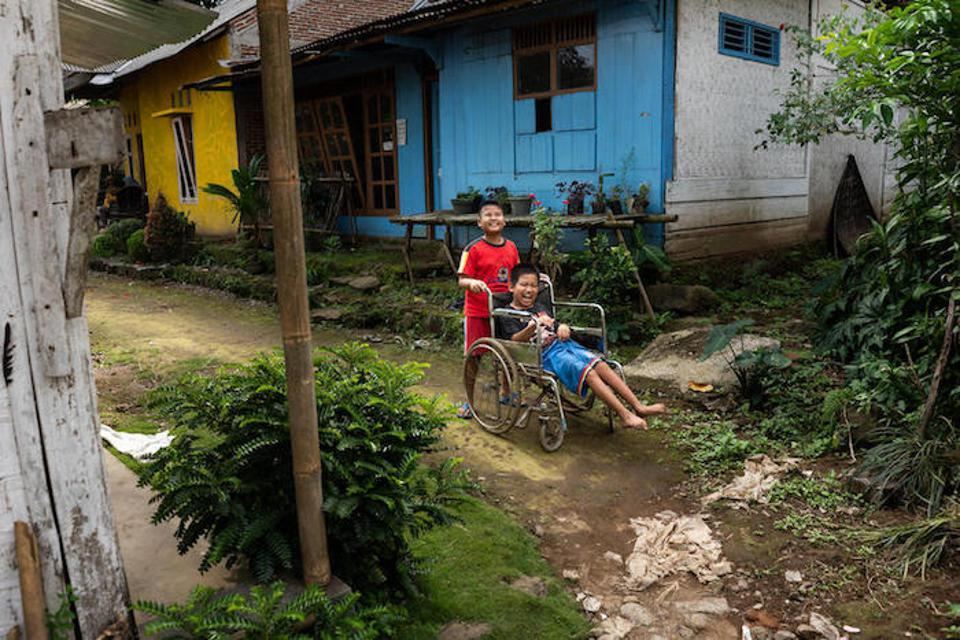 Kevin, 9, pushes his best friend, 12-year-old Syaiful, in his wheelchair as they play outside Syaiful's home in Banyumas, Central Java, Indonesia.