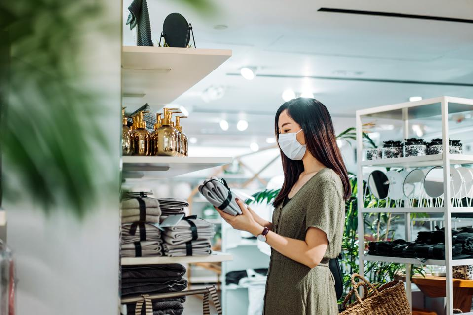 Young Asian woman with protective face mask shopping for household necessities in a homeware store looking at a pack of towels