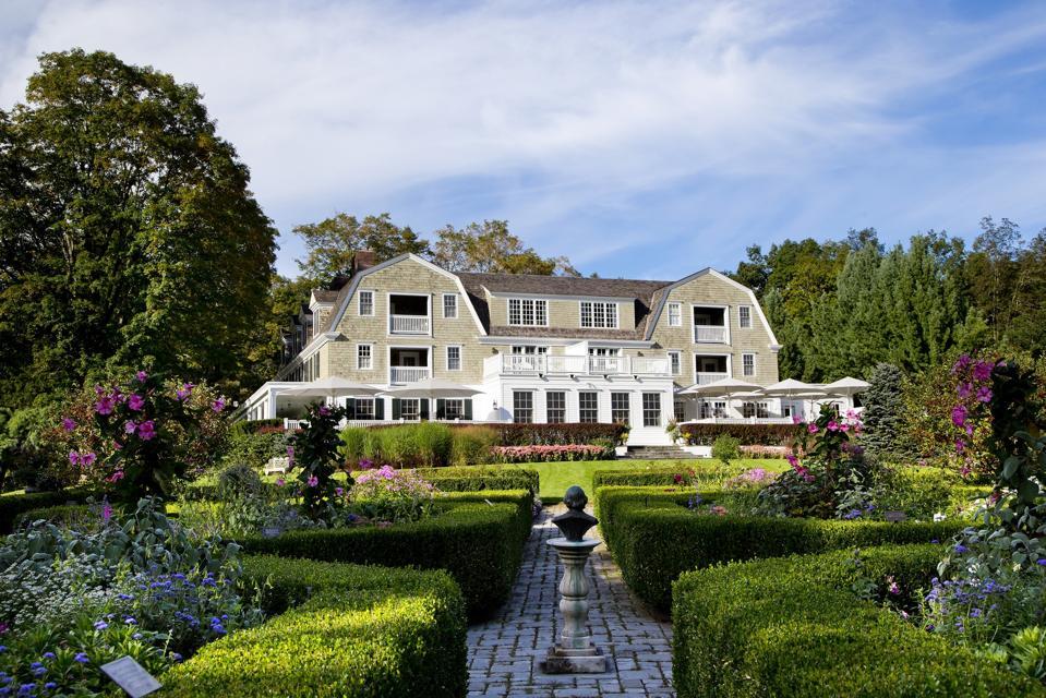 An elegantly shingled inn with lush gardens