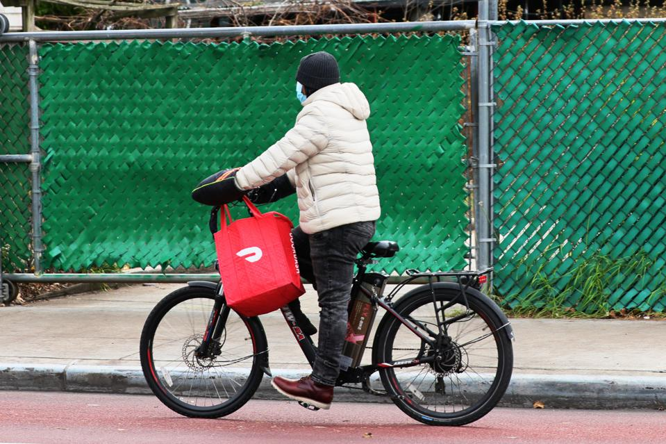 A DoorDash delivery worker rides their bike in Brooklyn in December 2020 as the business plans to go public.