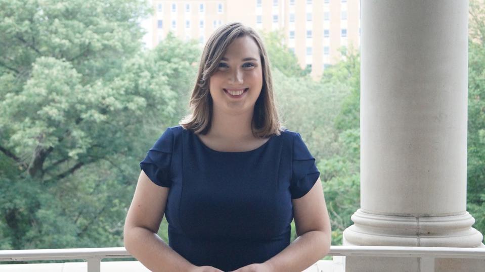 A white woman smiles wearing a navy blue dress.