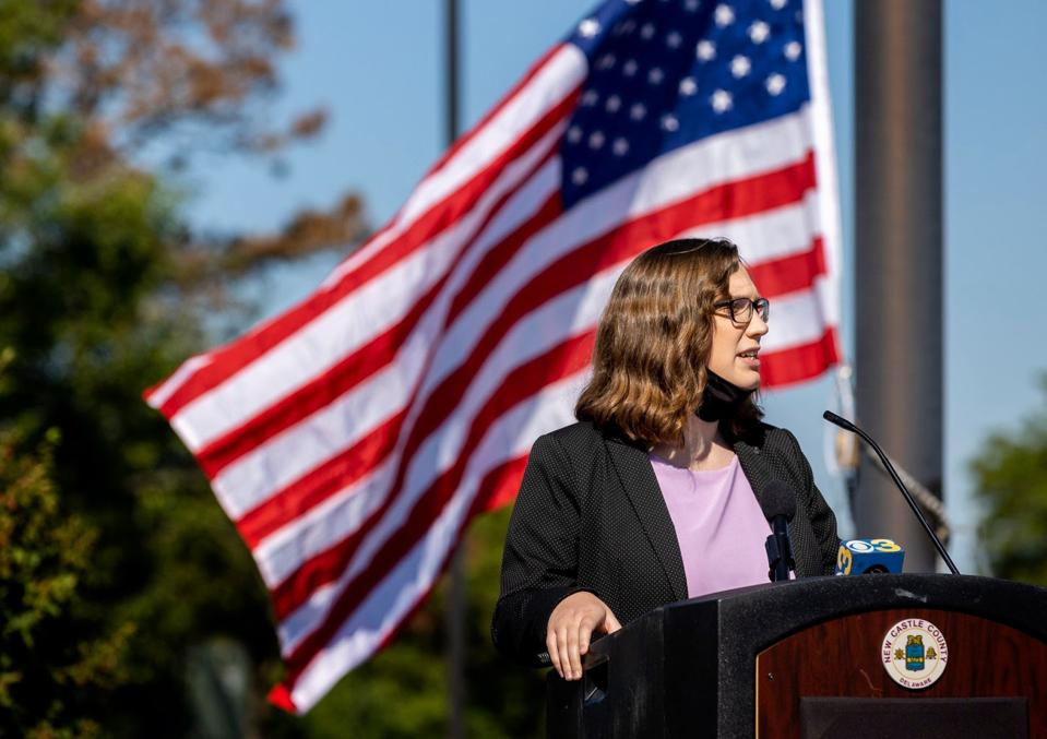 A woman at a podium in front of an American flag,