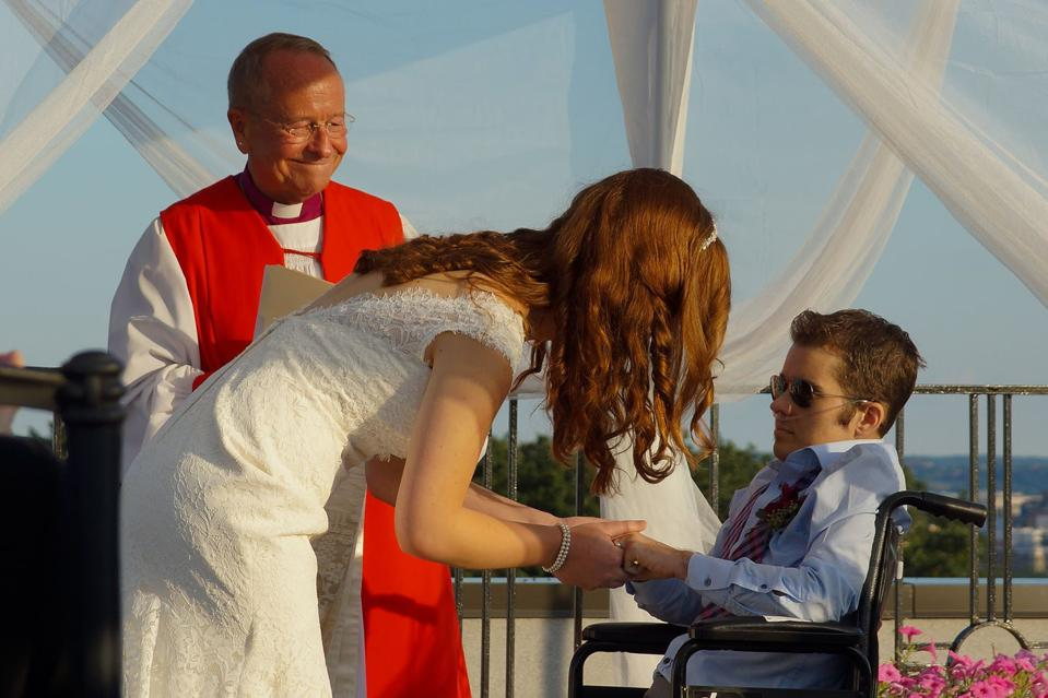 A woman in a wedding dress and a man in a wheelchair get married.
