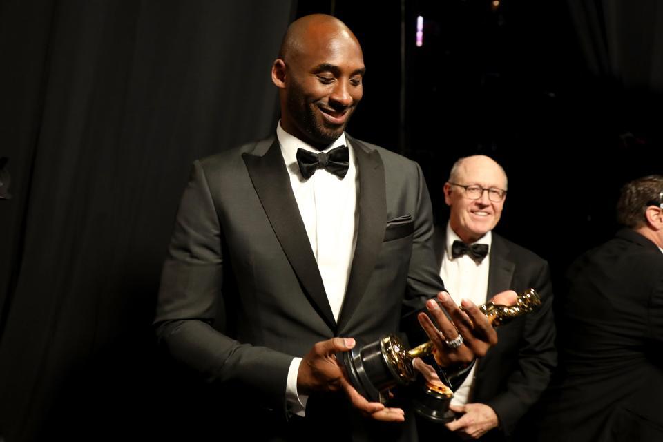 Kobe Bryant holding Academy Award.