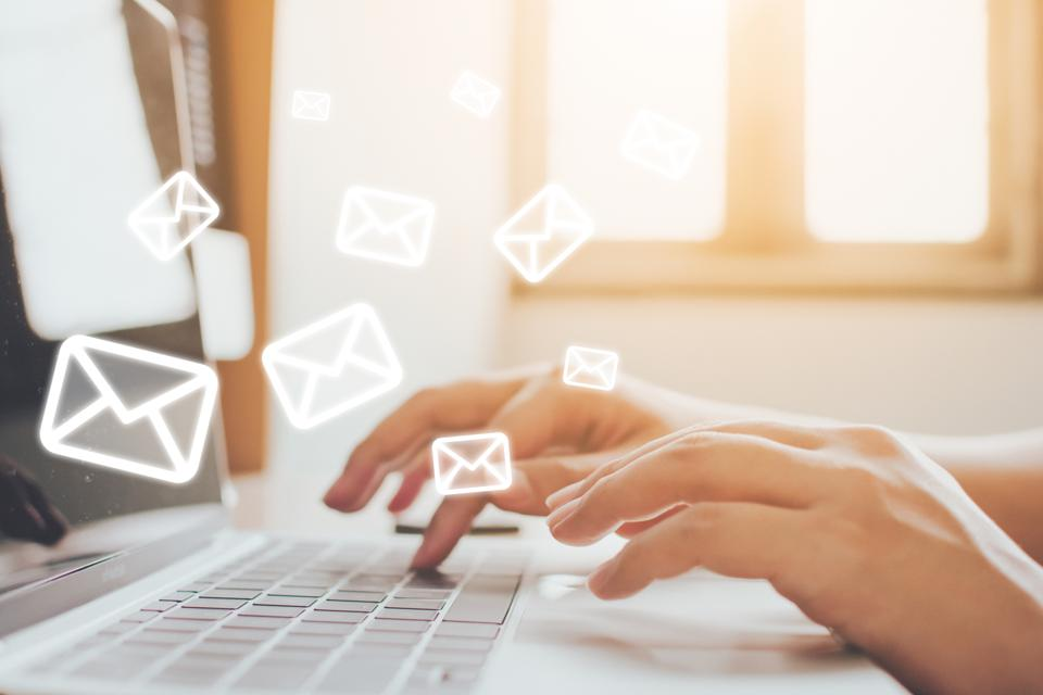 Email marketing and newsletter concept. Hand of man sending message and laptop with e-mail icon