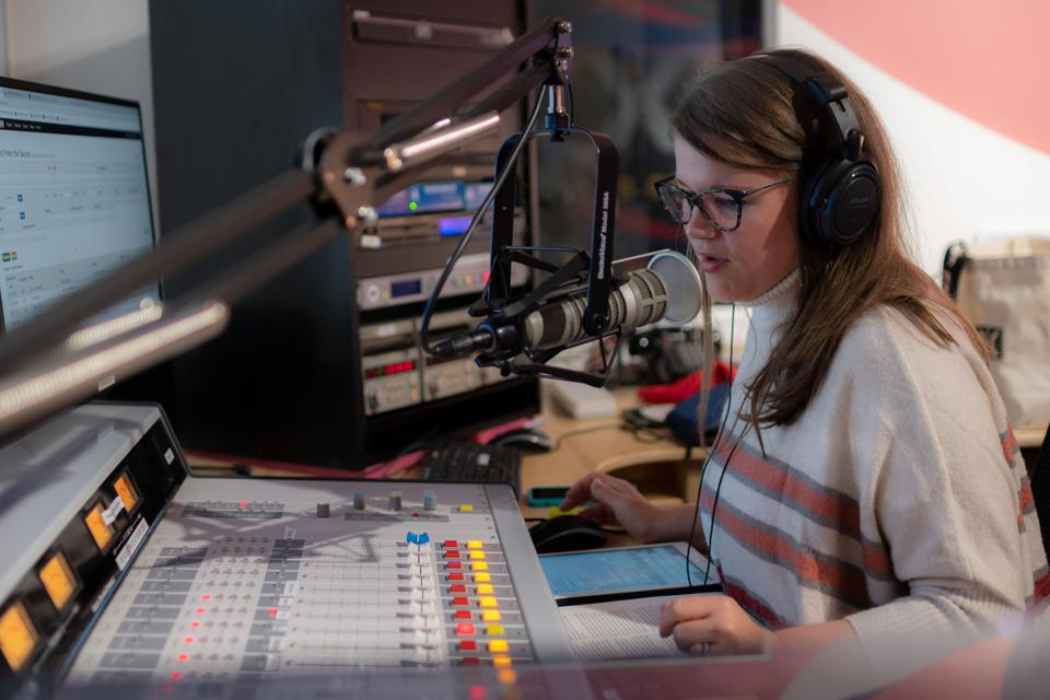 A young woman talks into a microphone in a radio studio.