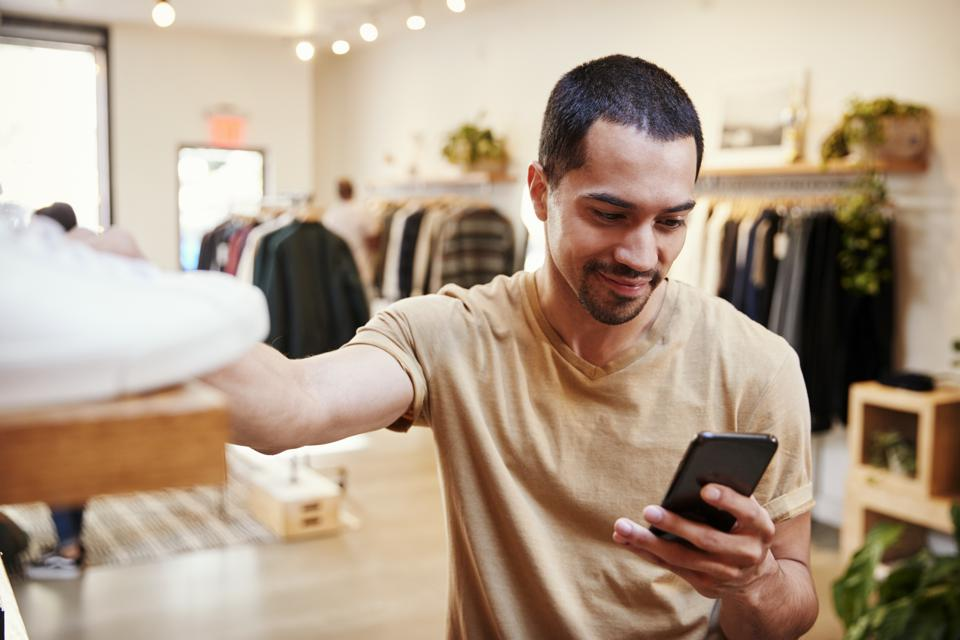 Smiling man using smartphone in a clothing store