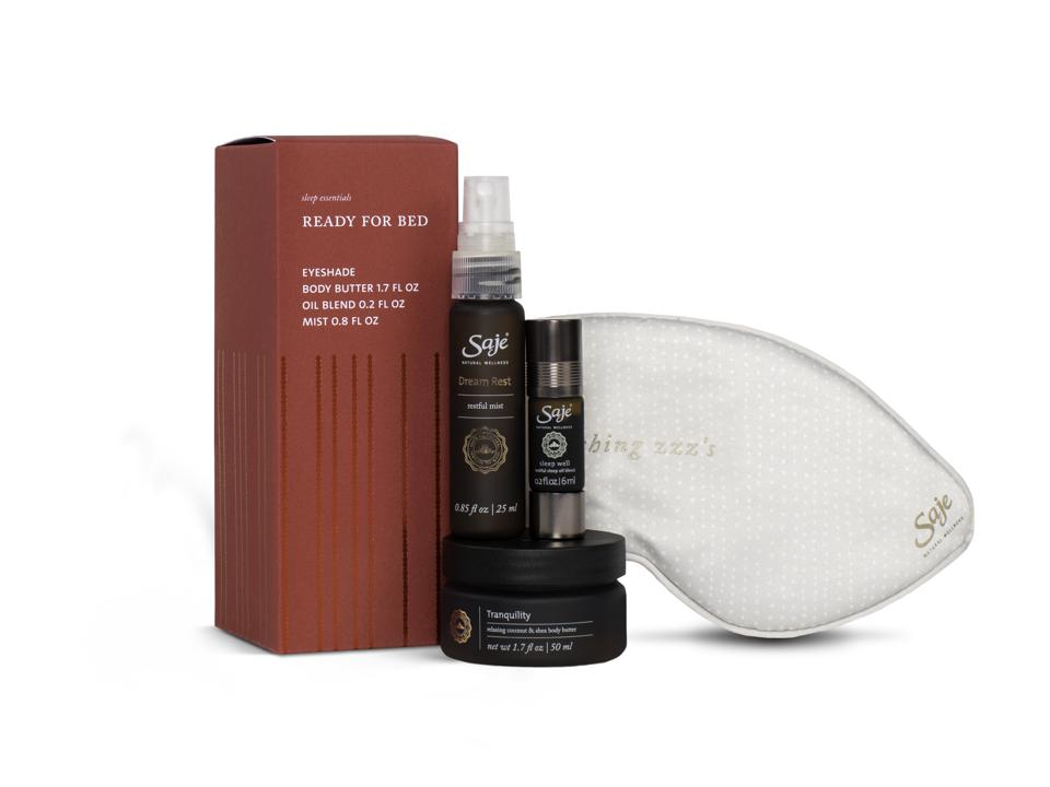 Saje sleep mask, essential oil roll-on, pillow mist and body cream against white backdrop.